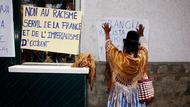 Eine Bolivianerin protestiert in La Paz und klebt Poster an die französische Botschaft.