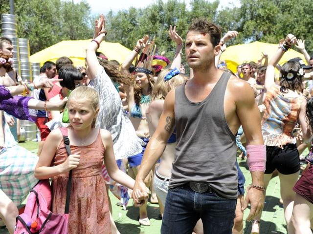 Ein Mann und ein Mädchen gehen Hände haltend und ängstlich blickend durch eine ausgelassene Menschenmenge.