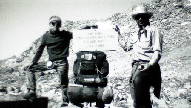 Ein alter und ein junger Mann halte eine Schrifttafel, die sie auf einem Rucksack abstützen.