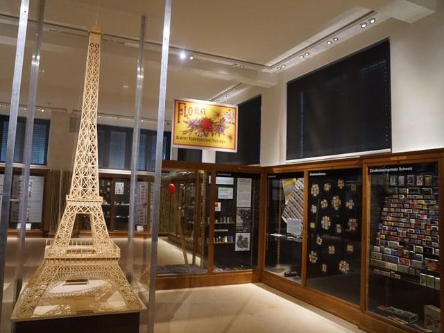 Links im Bild steht eine Miniaturversion des Eiffelturms, aus feinen Zündhölzern gebaut, daneben sieht man Vitrinen.