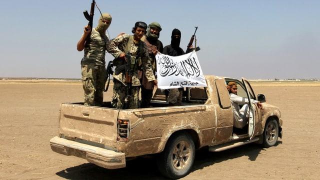 Männer mit Gewehren auf einem Pick-up.