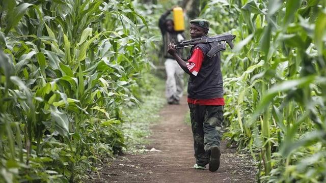 Person auf einem Feldweg mit Waffe.