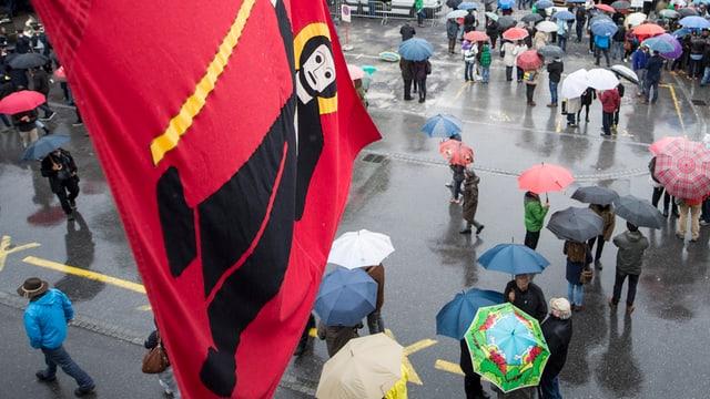 Fridolin-Fahne, Menschen mit Regenschirmen.