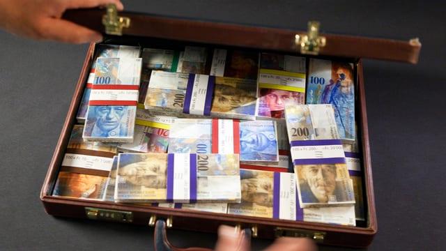 Symbolbild: Ein Koffer voller Schweizer Banknoten in Bündeln.
