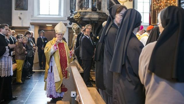 Ein Bischof in einer vollen Kirche, er blickt in die Kamera.
