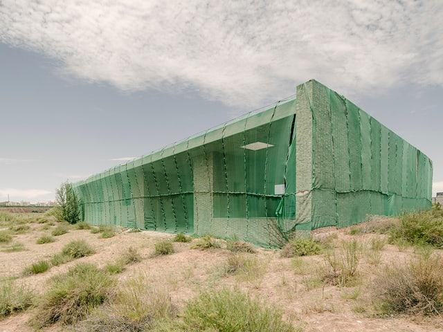 Ein grünes, kubisches Gebäude in einer kargen Landschaft.