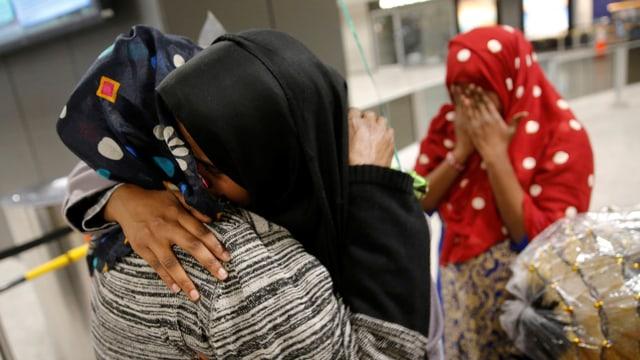 Muslima umarmen sich verzweifelt im Flughafen