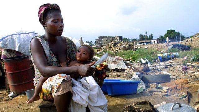 Eine Frau und ein Kind auf einem Platz mit viel Abfall.