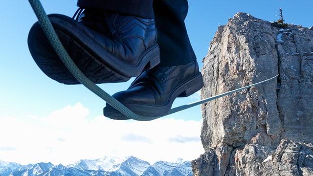 Füsse auf einem Seil, das an einem Berg befestigt in der Luft gespannt ist.
