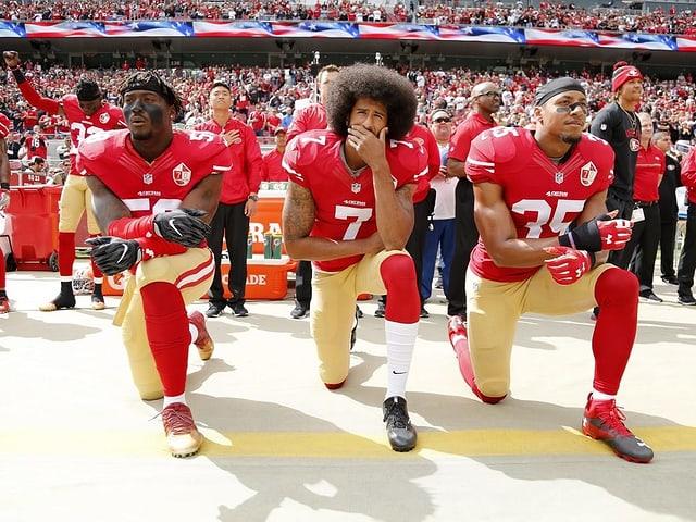 Colin Kaepernick (Mitte) und zwei seiner Teamkollegen gehen während der US-Hymne in die Knie.