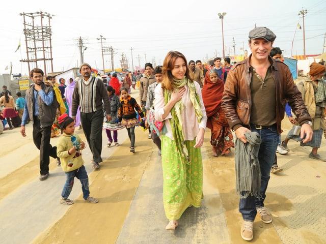 Ein europäisches Paar in indischer Kleidung, vor einer Menschenmenge.