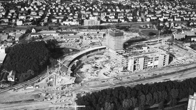 Eine Schwarz-Weiss-Aufnahme einer Baustelle zeigt ein grosses Gebäude neben einer Autobahn.