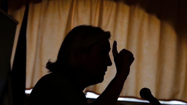 Gegenlicht-Aufnahme von Marine Le Pen, die in ein Mikrofon spricht und mit der Hand gestikuliert.