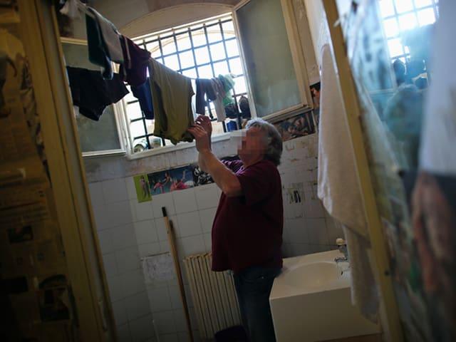 Ein Insasse hängt in der Zelle Wäsche auf