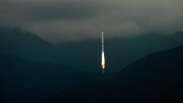 Eine Rakete beim Start in einer hügligen Landschaft.