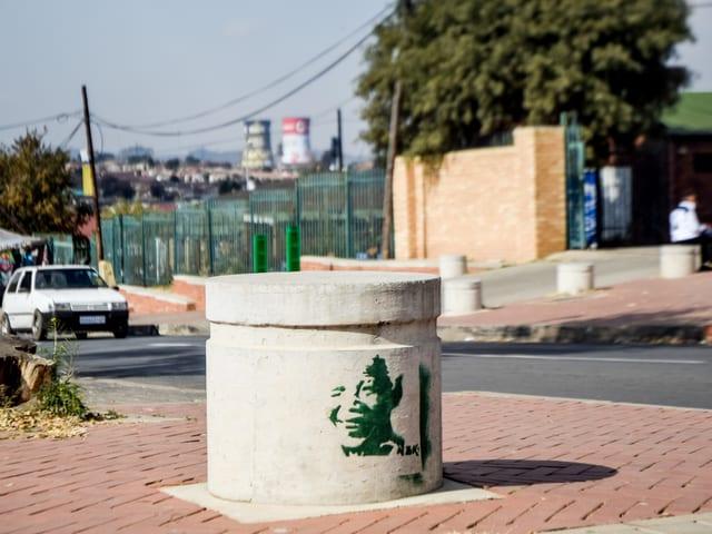 Schablonekunst, die Mandela zeigt, an einem Poller.