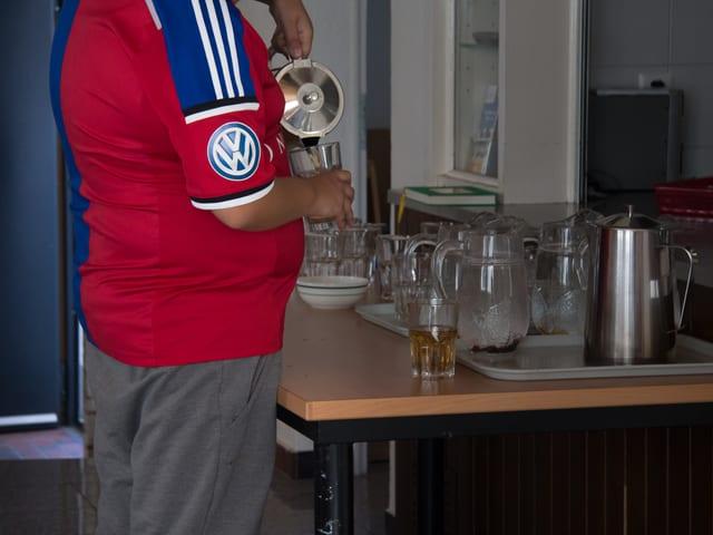 Ein Junge im FCB-Shirt schenkt sich Tee ein.