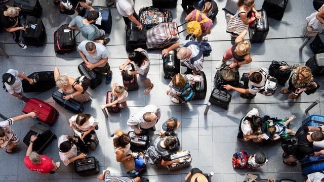 Menschen mit Koffern von oben gesehen.