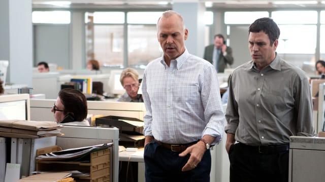Zwei Männer stehen in einer Zeitungsredaktion und reden miteinander.