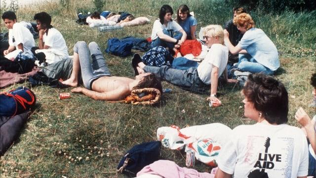 Jugendliche sitzen auf eine Wiese, ein Mädchen trägt ein Live Aid Shirt.