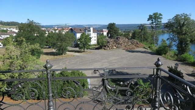 Fotografie vom Balkon her, grosse Teerfläche, im Hintergrund Lauf des Rheins