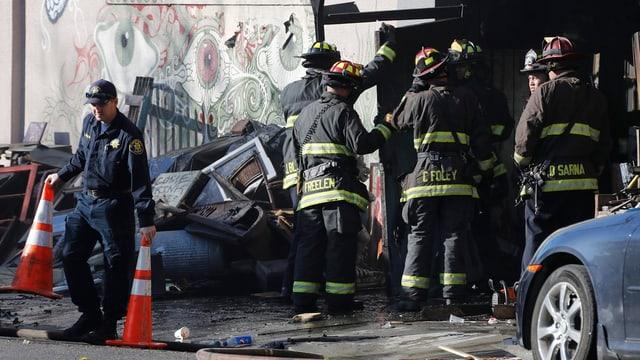 Feuerwehrleute vor einer verkohlten Hauswand.