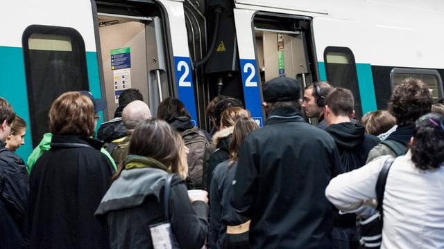Zahlreiche Pendler drängen in einen Regionalzug 2. Kalsse.