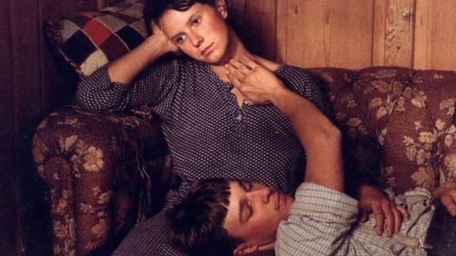 Ein Junge kniet vor einem schlafenden Mädchen und hält ihre Hand.