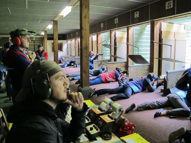 Schützen liegen im Schiessstand.