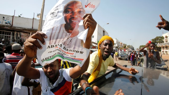 Männer feiern auf der Strasse mit Wahlplakaten.