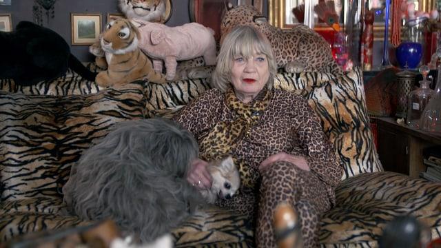 Eine Frau im Leopardenkostüm sitzt auf einem Sofa mit Zebramuster. Sie streichelt einen Hund. Auf dem Sofa liegen Stofftiere, darunter ein Tiger und ein Schwein.