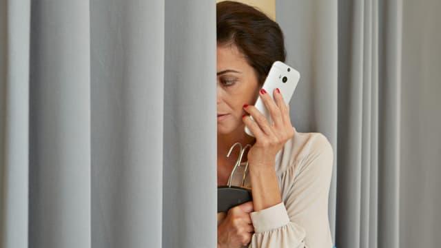 Eine Frau am Handy, das halbe Gesicht hinter einem Vorhang versteckt.