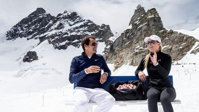 Roger Federer und Lindsey Vonn sitzuen auf einer Bank auf dem Jungfraujoch, zwischen ihnen eine Tasche voller Lindt-Schoggi.