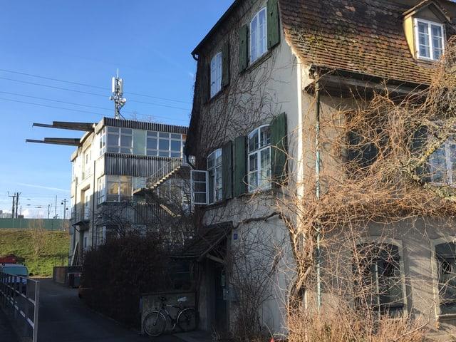 Eine Fabrikhalle steht hinter einen alten Haus.