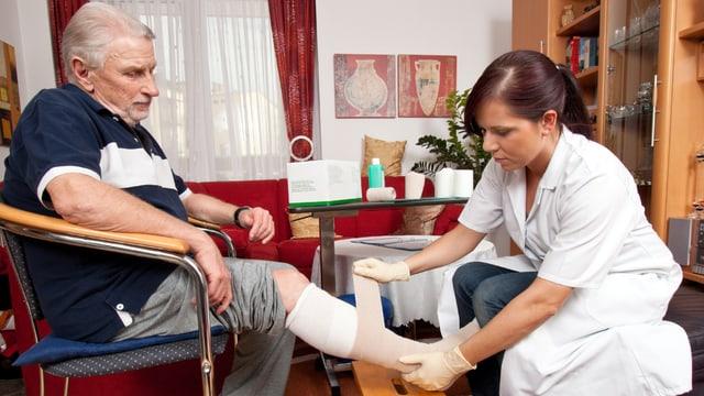 Pflegerin legt älterem Mann Verband am Bein an