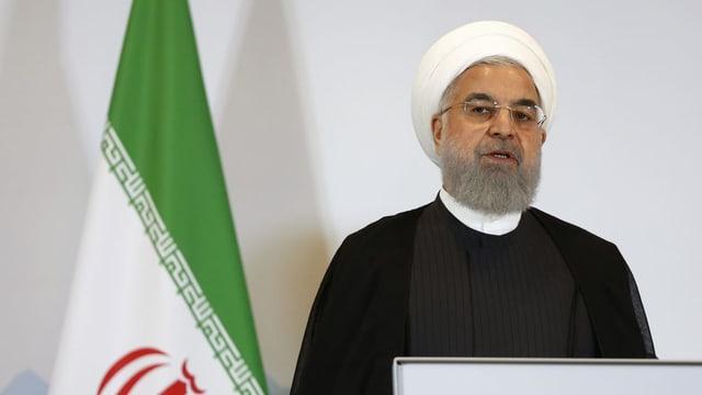 Mann vor Iranflagge.