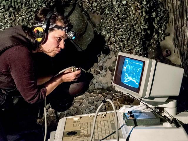 Frau steht neben einer schuppigen Fläche und untersucht diese mit einem Ultraschallgerät.