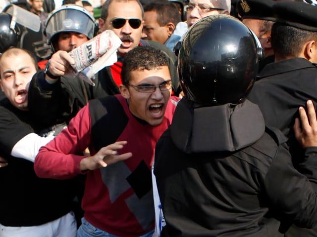 Ein Polizist in schwarzer Schutzkleidung und Helm schreitet gegen die wütende Masse in Kairo ein, ein junger Ägypter in bordaux-farbenem Pullover will sich auf den Polizisten stürzen.