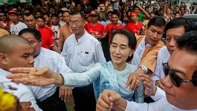 Aung San Suu Kyi in einer Menschenmenge. Sie nimmt Blumen eines Anhängers entgegen.