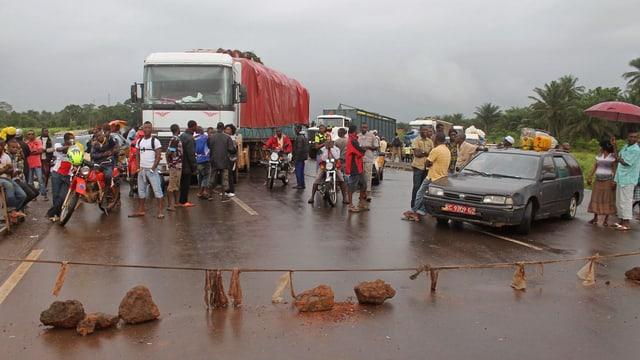 Mit Seil blockierte Strasse, dahinter Auto, Lastwagen und Menschen.