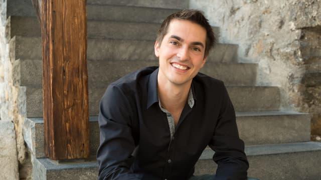 Ein junger Mann im schwarzen Hemd sitzt lächelnd auf einer Treppe.