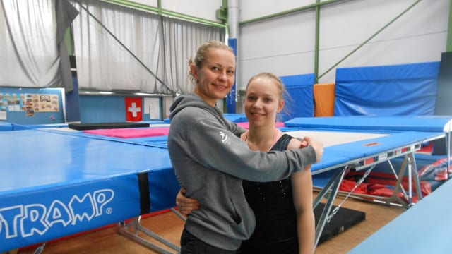 Trainerin umarmt eine Trampoliln-Springerin in einer Trainingshalle für Trampolin.