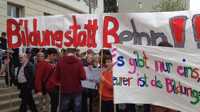 Mehrere Personen demonstrieren mit Transparenten vor dem Parlamentsgebäude