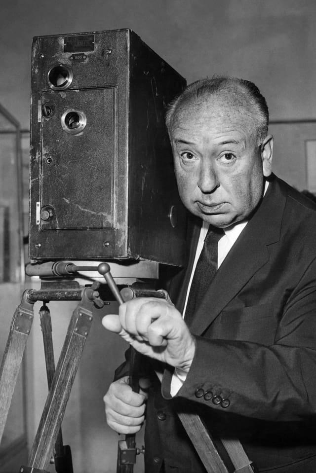 Alfred Hitchcock posiert hinter einem alten Projektionsgerät.
