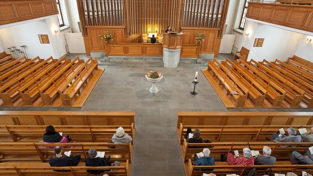 Blick in eine reformierte Kirche während einer Predigt. Die Sitzbänke sind fast leer.