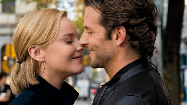 Eine blonde Frau und ein dunkelhääriger Mann küssen sich.