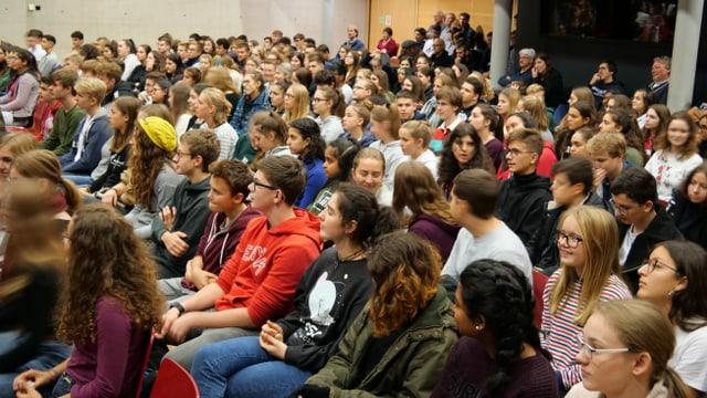 Junge Frauen und Männer versammelt in einem grossen Saal