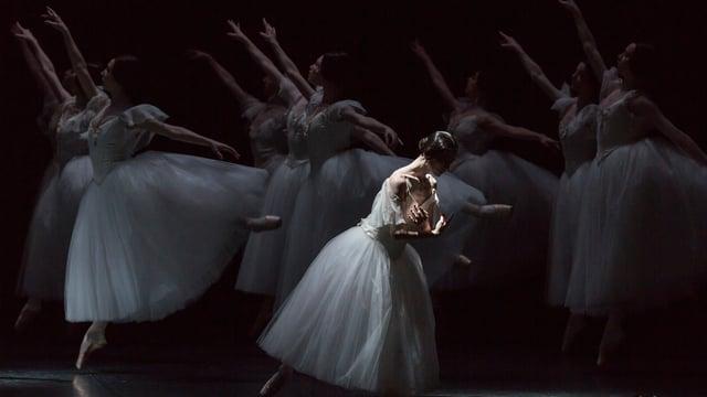 Ein Balettänzerin in weissem Kleid, dahinter im Schatten weitere Tänzerinnen.