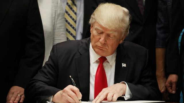 Purtret da Trump che suttascriva il decret.