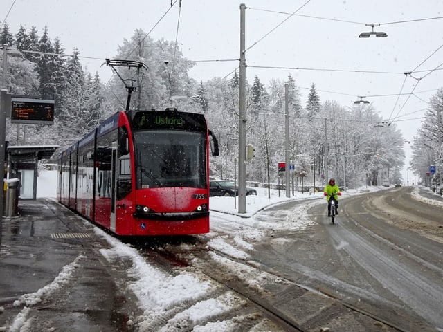 Schnee in Bern, eine Strassenbahn fährt zur Haltestelle, auf der Strasse liegt Schneematsch.